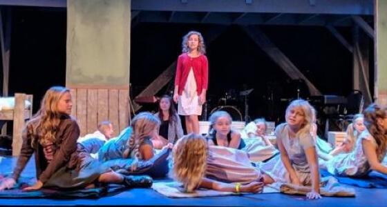 """""""Annie"""" standing in a circle of peers, singing."""